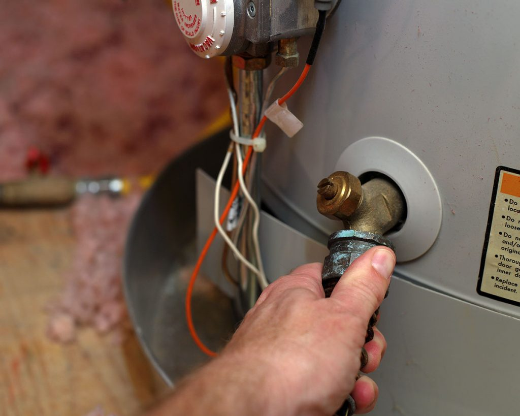 Hand Attaches Hose To Water Heater