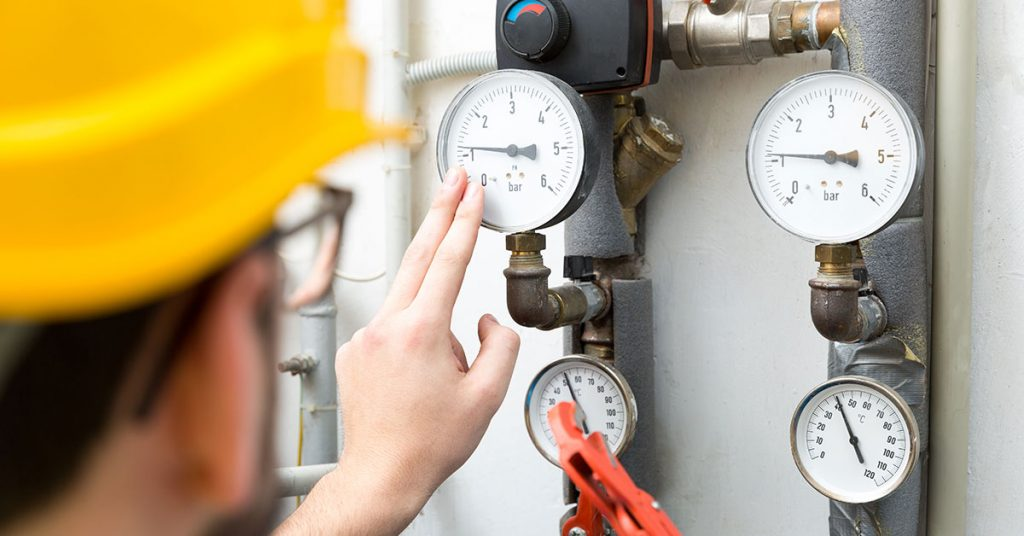 Maintenance Technician Checking Pressure Meters For House Heating System